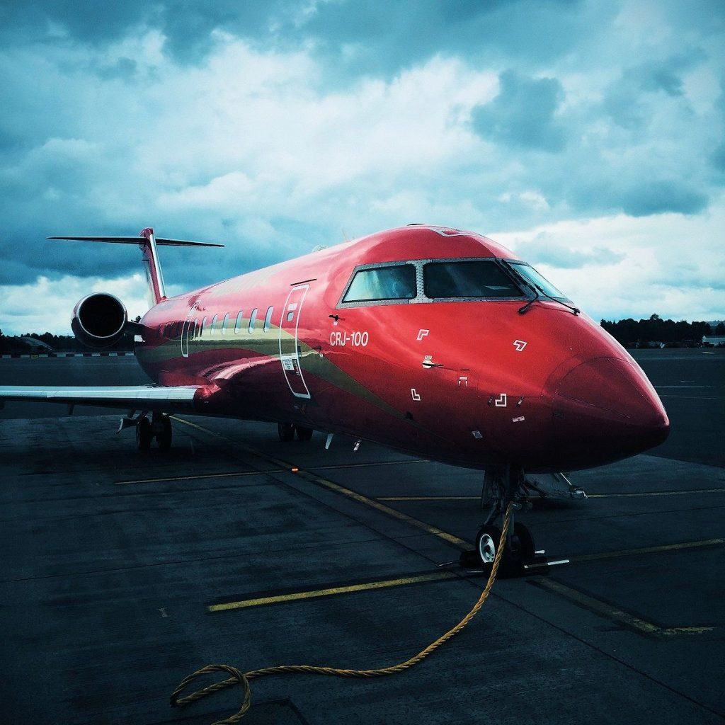 Red jet parked at airport. Euro 2020 is only a short flight away.