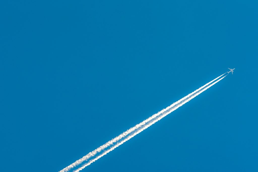 Jet leaving condensation tracks in the blue sky. Flying on a private jet is the most convenient way to reach the Euro 2020 venues.