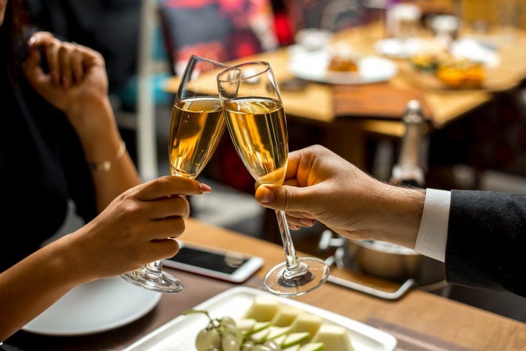 Couple Join Two Tall Glasses of Champagne Dining Out